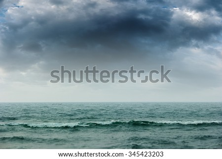 Gray storm clouds over the blue ocean making rough seas and a dramatic seascape. - stock photo