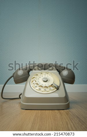 Gray vintage phone on hardwood floor and dotted light blue wallpaper on background. - stock photo