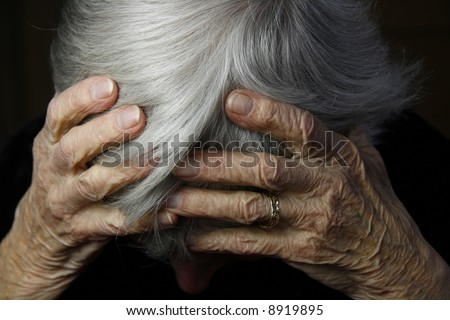 grayed haired lady holding head in severe pain - stock photo