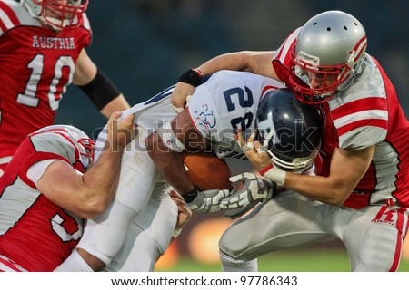 GRAZ, AUSTRIA - JULY 13: RB Laurent Marceline (#28 France) is tackled at the Football World Championship on July 13, 2011 in Graz, Austria. France wins 24:16 against Austria. - stock photo