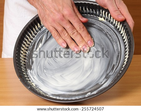 Grease pan with butter. Making Apple Pie Tart Series. - stock photo