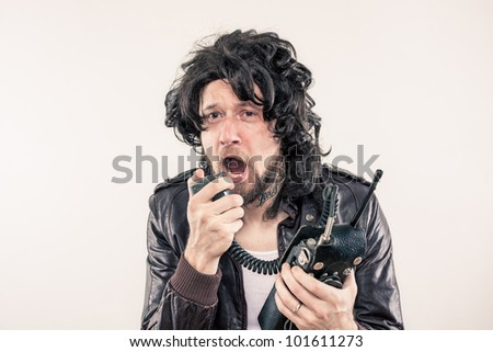 Greasy undercover agent freaking out on vintage wireless radio in the middle of a crises - stock photo