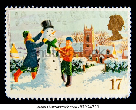 GREAT BRITAIN - CIRCA 1990: A stamp printed in Great Britain shows children are building a snowman, series is devoted to Christmas, circa 1990 - stock photo
