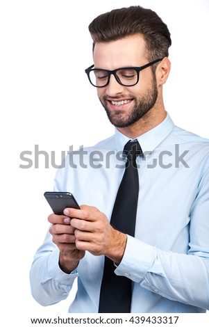 Great business news! Confident young handsome man in shirt and tie holding mobile phone and looking at it with smile while standing against white background  - stock photo