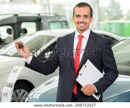 Great choise! Handsome young classic car salesman standing at the dealership holding a key - stock photo