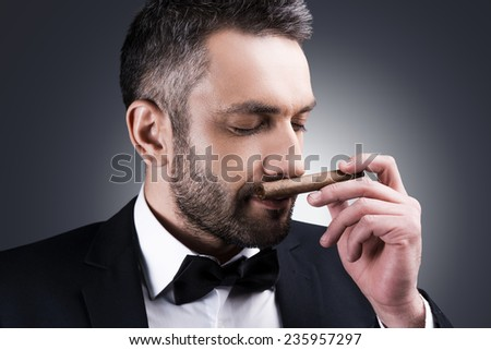 Great cigar! Portrait of handsome mature man in formalwear smelling cigar and keeping eyes closed while standing against grey background - stock photo