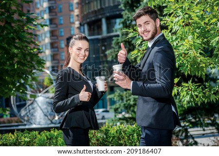 Great coffee break. Confident businessman and successful business woman drinking coffee outside the business center and looking at each other. Businesspeople in formal attire - stock photo