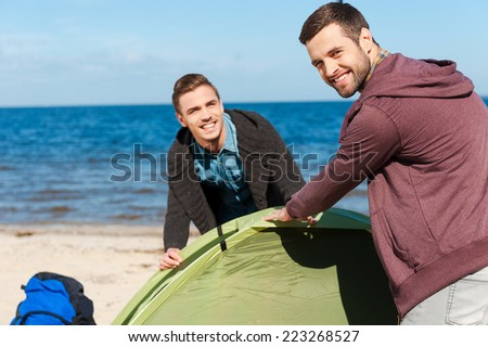 Great day for camping. Two cheerful young men setting up a tent and smiling while standing at the riverbank  - stock photo