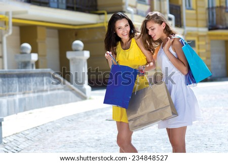 Great deal while shopping sales. Two young and attractive girls are smiling and standing with shopping bags on the street after going shopping - stock photo