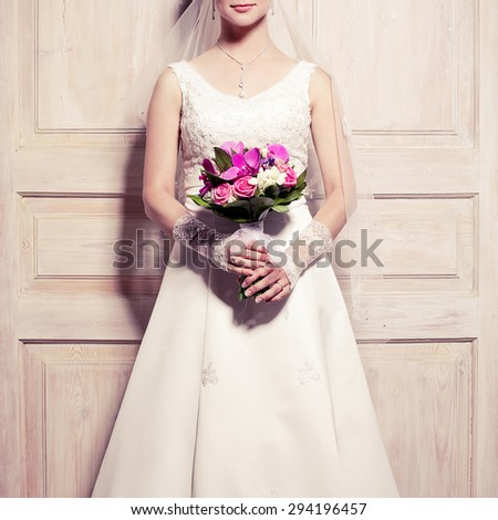 Great event, wedding bouquet concept. Bride holding bouquet of leaves, roses, orchid blossom, buds over wooden doors. Luxurious accessories. Pastel colors. Classic retro style. Indoor shot - stock photo