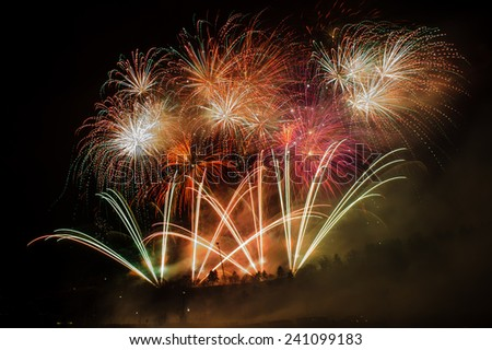 Great fireworks celebration of new year on dark night sky. Full of colors and sparkling stars. - stock photo