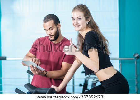 Great fitness workout. Athletic girl pedaling on a stationary bike in the gym while trainer on the tablet shows how to pedal. Girl showing thumbs up - stock photo