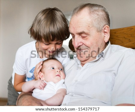 Great grandfather holding a new born baby girl next to his school age grandson - stock photo
