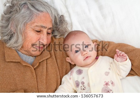 Great Grandma and great granddaughter snuggling on white sheet - stock photo