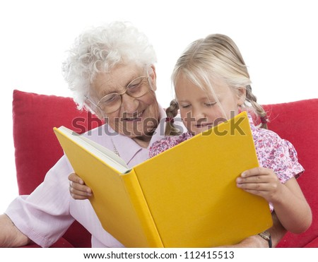 great grandmother and great granddaughter reading a book together - stock photo
