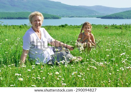 Great grandmother and her great granddaughter in spring blooming meadow with chamomiles. - stock photo