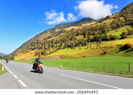 Great Highway in Austrian Alps. Among the picturesque hills at high speed riding two motorcycles biker - stock photo
