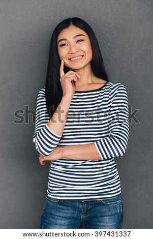 Great idea! Beautiful young Asian woman keeping hand on chin and looking away with smile while standing against grey background - stock photo