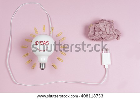 great idea concept with crumpled colorful paper and light bulb on light background. Creative brainstorm concept business idea.  Copy space for text. - stock photo