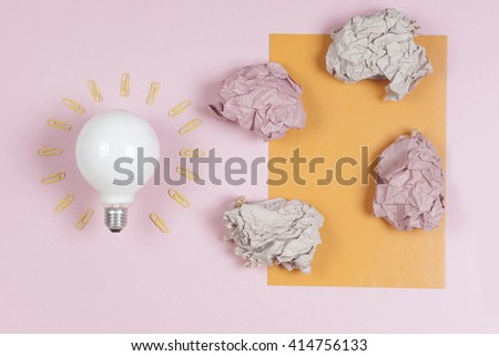 great idea concept with crumpled colorful paper and light bulb on light background. Creative brainstorm concept business idea.  female hand holding light bulb. Copy space for text. - stock photo