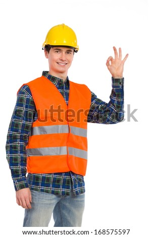 Great job done! Smiling construction worker in yellow helmet and orange waistcoat showing ok sign. Three quarter length studio shot isolated on white. - stock photo