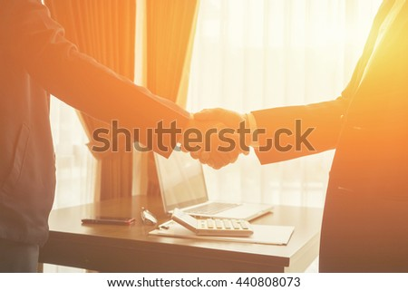 Great job,Sealing a deal,Successful business,Handshake,Business man holding hands,Good deal.two business people shaking hands standing at the working place,selective focus,Vintage tone,copy space - stock photo