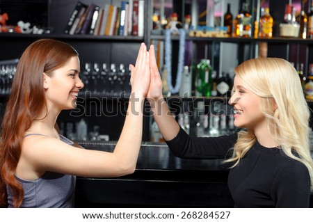 Great job. Two beautiful smiling girls clapping their hands delighted and cheerful - stock photo