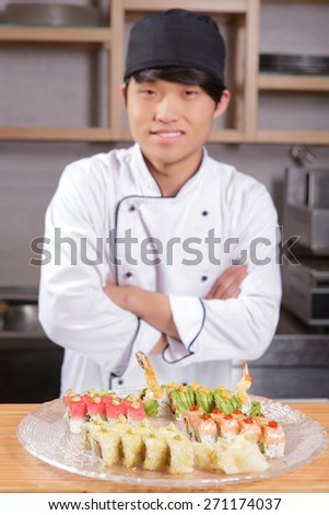 Great job. Young cheerful Asian cook standing with his arms crossed before the big dish with different kinds of sushi rolls - stock photo