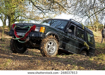 GREAT MALVERN, UK - DECEMBER 8: An unnamed driver competing in the SCOR UK trials championship negotiates a steep ditch and leafy bank at the Croft Farm round on December 8, 2013 in Great Malvern - stock photo