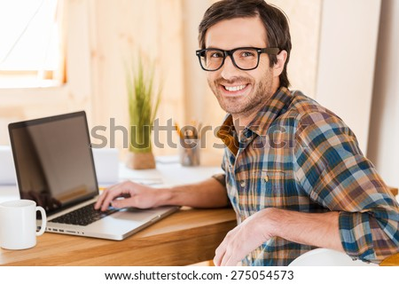 Great mood for working good. Handsome young man working on his laptop and looking at camera over shoulders while sitting at his working place - stock photo