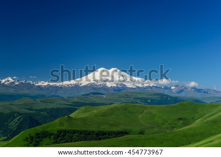 Great nature mountain range. Amazing perspective of caucasian snow mountain Elbrus with green fields, blue sky background. mountain Elbrus landscape view. - stock photo