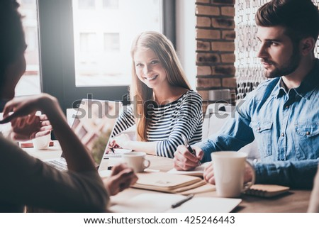 Great news! Cheerful young woman looking at camera with smile while sitting at the office table at the business meeting with her coworkers - stock photo