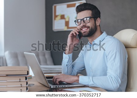 Great news! Handsome cheerful young man wearing glasses talking on mobile phone and looking away with smile while sitting at his working place - stock photo