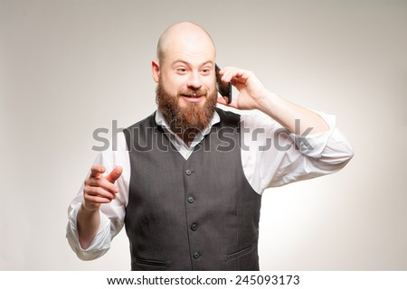 Great news! Happy young bearded man talking on the mobile phone and gesturing while standing against grey background - stock photo
