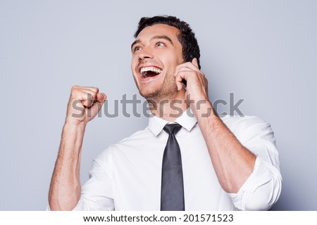 Great news! Happy young man in shirt and tie gesturing and smiling while talking on the mobile phone and standing against grey background  - stock photo