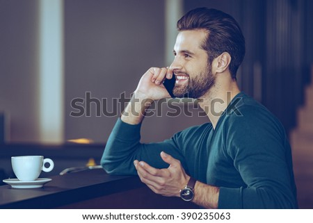 Great phone call. Side view of handsome young man talking on mobile phone with smile while sitting at bar counter - stock photo