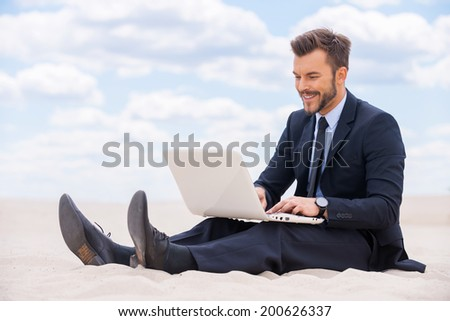 Great place to work. Cheerful young man in formalwear working on laptop while sitting on sand in desert - stock photo