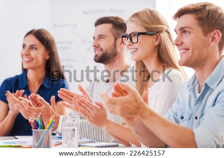 Great presentation! Group of happy business people in smart casual wear sitting together at the table and applauding to someone - stock photo