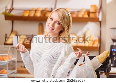 Great purchase. Beautiful female customer posing with a credit card and her purchase at the cash desk against rows of fresh baked bread - stock photo