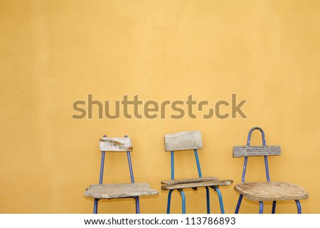 Great recycled  chairs design, with beautiful yellow hand painted wall background - stock photo