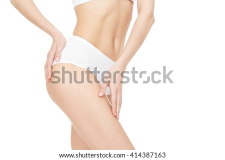 Great shape. Cropped studio shot of a fit female model showing off her flat stomach posing touching her upper leg isolated on white copyspace on the side. - stock photo