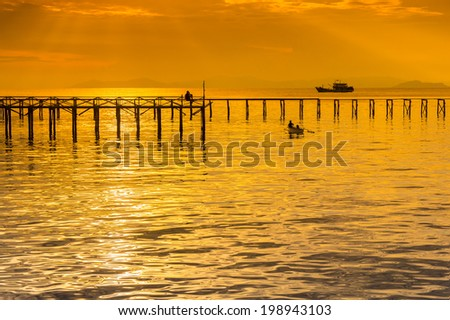 great silhouette jetty and golden seascape - stock photo