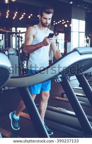 Great song for his exercising. Full length of young handsome man in sportswear using his smart phone while walking on treadmill at gym - stock photo