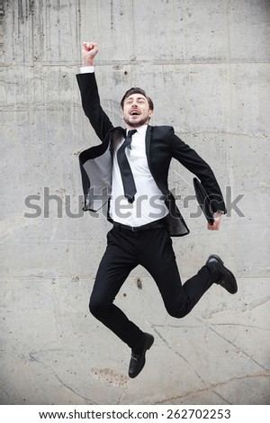 Great success. Happy young man in formalwear keeping arms raised and expressing positivity while jumping in front of the concrete wall  - stock photo