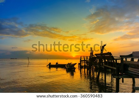 great sunset and silhouette wood jetty - stock photo