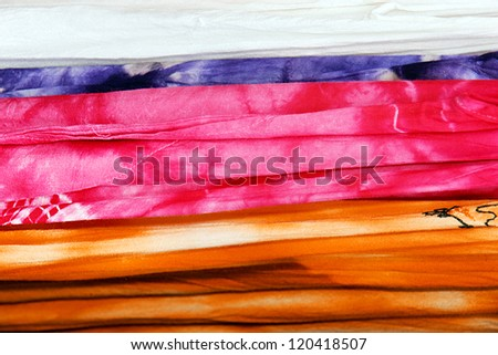 Great texture background made with tie dye cotton fabrics in bright pink, orange and purple. - stock photo