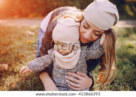 great trendy young mothers walking in the park with his daughters in beautiful clothing - stock photo