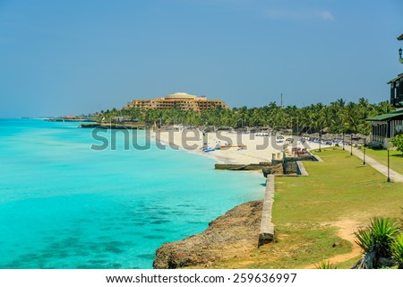 great view of amazing, gorgeous inviting tropical beach with people in background on sunny summer day - stock photo