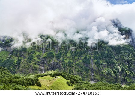 Great view of green mountain canyon and little house at the edge of meadow - stock photo