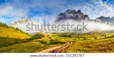 Great view of the foggy Tofane mountain range from Falzarego pass. National Park. Dolomites (Dolomiti), South Tyrol. Location Cortina d'Ampezzo. Italy, Europe. Dramatic scene. Beauty world. - stock photo